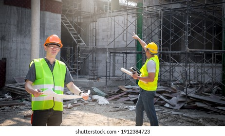 Architect, Engineer, Contractor, or Construction manager holding blueprint standing with a group at a construction site.
