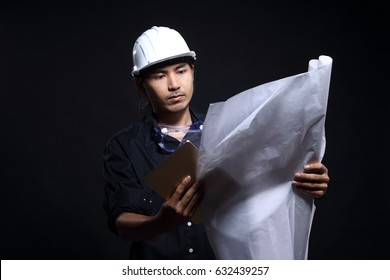 Architect Engineer in dark blue shirt white hard hat and blueprints roll check with tablet, studio lighting black background copy space, rim light from back