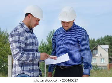 Architect and engineer having a discussion referring to a paper document as they stand on a building site in their hardhats