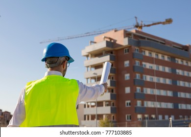 Architect or Engineer holding blueprints on the Construction Site.  Daytime. Wearing protection equipment