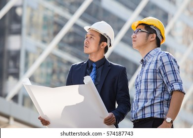 Architect, engineer, project manager or businessman point to building in the city with a blank plan as for construction