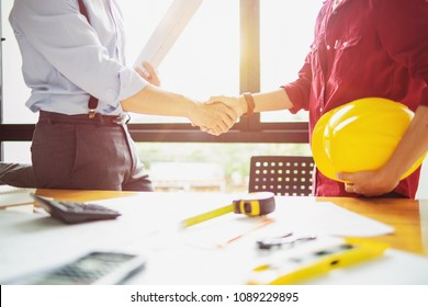 architect engineer shaking hands beside window - business teamwork, cooperation, success collaboration concept