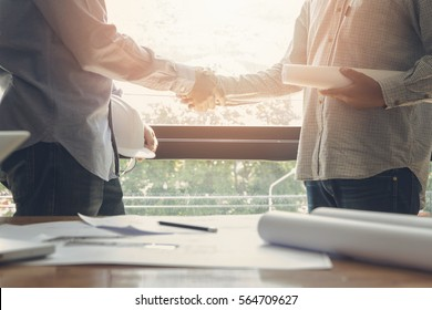 Architect and engineer shaking hands beside the window