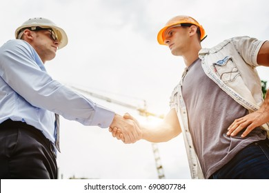 Architect engineer shaking hands other hand at construction site.  Business teamwork, cooperation, success collaboration concept