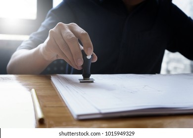 Architect or engineer stamping the document or blueprint on wooden desk - architectural project, Construction concept.