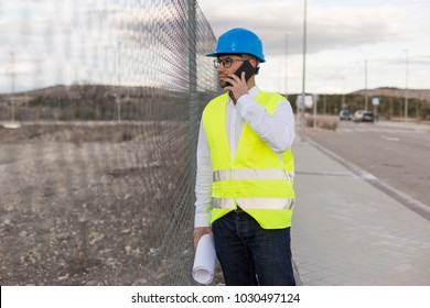 Architect or Engineer talking on his mobile phone on the construction site. Job concept. Wearing protective clothes
