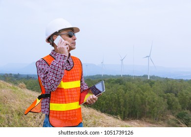 Architect or Engineer use Mobile smartphone while hold Wireless Tablet Device in Field of Wind Turbine Power Generator as Outdoor Technology Equipment for Working Concept.