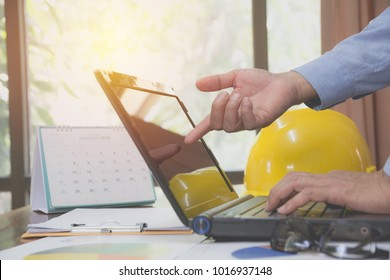 Architect engineer using laptop for working with yellow helmet on desk.