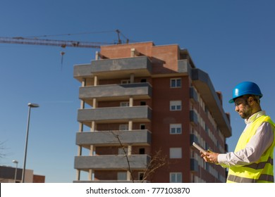 Architect or Engineer using tablet on the Construction Site. holding blueprints Daytime. Wearing protection equipment