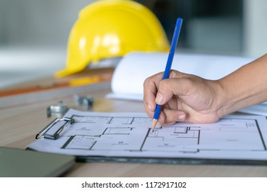 Architect & Engineer working drawing document about project planning and progress of work schedule on the home building construction site ,