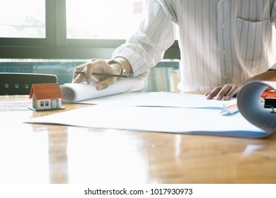 Architect or engineer working in office with blueprints,engineer inspection in workplace for architectural plan,sketching a construction project ,selective focus,Business construction concept.