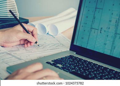 Architect or engineer working in office on blueprint. Architects workplace