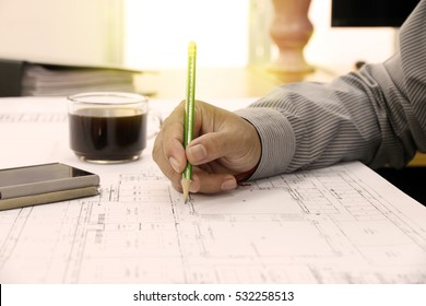 Architect or engineer working on blueprint and architecture mode in office room, Construction concept. Engineering tools.