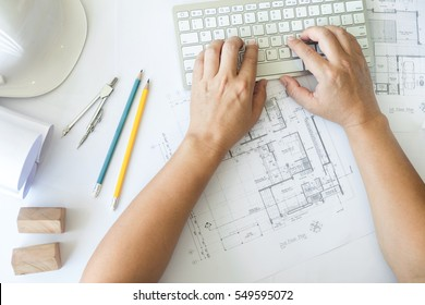 Architect or engineer working on keyboard blueprint and architecture mode in office room, Construction concept