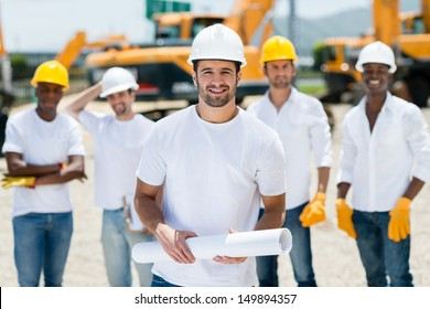 Architect with a group at a construction site holding blueprints