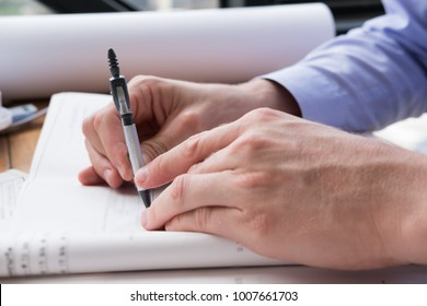 architect hand holding drawing compass working on construction plan at office. engineer inspect blueprint with divider at workplace. young man sketching real estate project