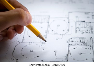 architect hand with pencil drawing blueprints