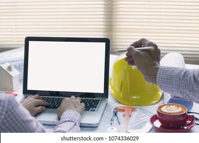 architect hands using laptop with a building of blueprint and engineering tools on working table.