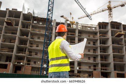 Architect in hardhat pointing at building under construction