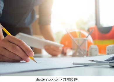 Architect holding pencil , plan tablet and blueprints background