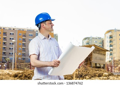 Architect holding a project and observe the construction site.