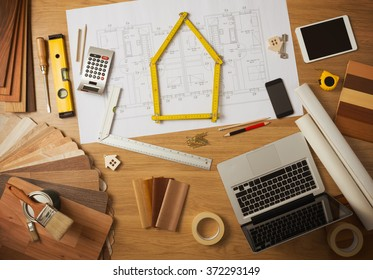 Architect and home interior decorator desktop with tools, laptop, wood swatches and home project draft top view, a meter is composing a house at center