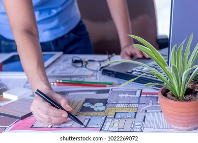 Architect, interior designer (Artist creative) working at table with drawing sketch, laptop computer in office / Home renovation, decoration & Real estate conceptual