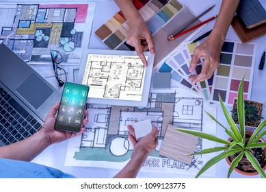 Architect, interior designer (Artist creative) working at table with smartphone, laptop, tablet computer & drawing sketch in office / Home renovation, decoration & technology conceptual