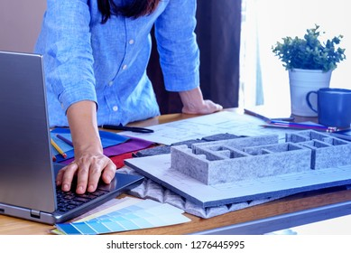 Architect -Interior designer (Artist creative) working with architecture model, material sample, laptop in office / Renovation, decoration & Real estate business conceptual