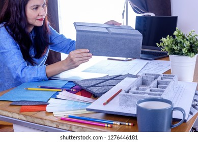 Architect -Interior designer (Artist creative) working with acoustic sample board, architecture equipment, model & laptop in office / Renovation, decoration & Real estate business conceptual