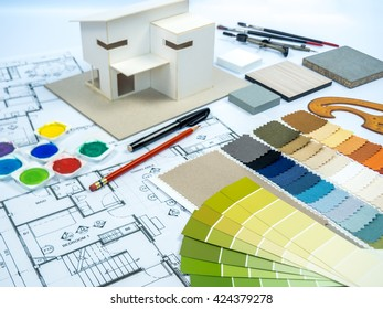 Architect, interior designer worktable with color swatch, home model, sketch, blue print & sample / Real estate business & home renovation  conceptual