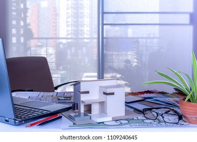 Architect, Interior designer's (Artist creative) worktable with home model, drawing sketch, laptop in office / Renovation, decoration & Real estate conceptual