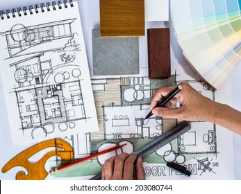 Architect /interior's hands drawing home illustration with material sample, renovation  concept
