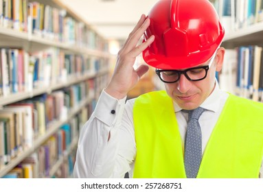 Architect man wearing a red helmet. He is looking tired. Over library background