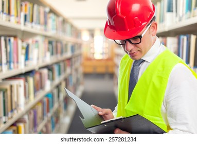 Architect man wearing a red helmet and reading from a black folder. Over library background