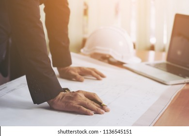 Architect man working with laptop and blueprints,Engineer sketching a construction project concept. ,selective focus