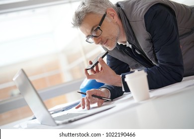 Architect in office talking on mobile phone