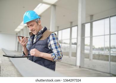 Architect on cellphone checking worksight progress