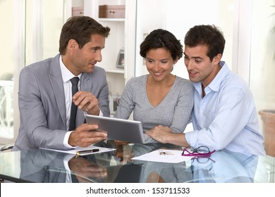 Architect presenting a new project to a smiling young couple