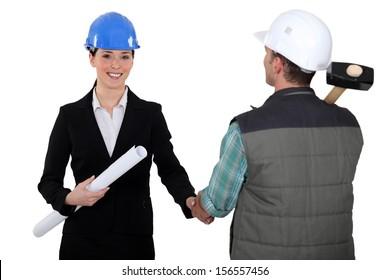 Architect shaking builders hand