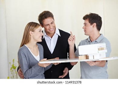 Architect showing 3D house model to smiling couple