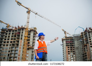 Architect showing buildings on a construction site during a housing project