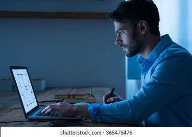 Architect sitting at night working on architectural plan on laptop. Young interior designer in casual checking blueprint of a house on laptop. Architect studying the map and layout of a new project.