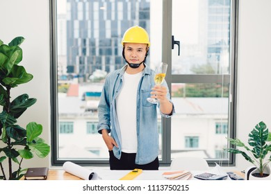 Architect sketching construction project on wooden table,holding glasses champange