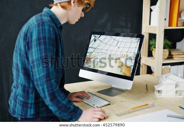 Architect standing in front of monitor with image of business hall