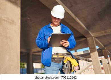 Architect standing studying a handheld blueprint on a construction site of a new build house.Handsome architect or supervisor standing outdoors on a building site holding a blueprint in his hands,