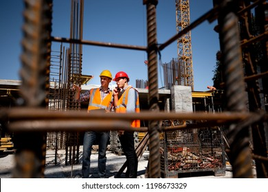 Architect  and structural engineer  in orange work vests and  helmets discuss a building project on the open air building site with a lot of steel frames