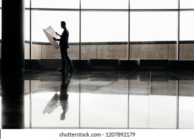Architect in stylish clothes holds sheet with drawing in his hand and talks by phone on the background of a modern glass multistory building