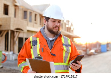 Architect surfing internet by smartphone and holding notebook on construction site. Concept of building house and real estate in USA.