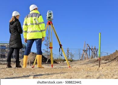 A Architect and surveyor on a construction site back sight